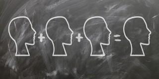 3 heads equal 1, written on a chalkboard
