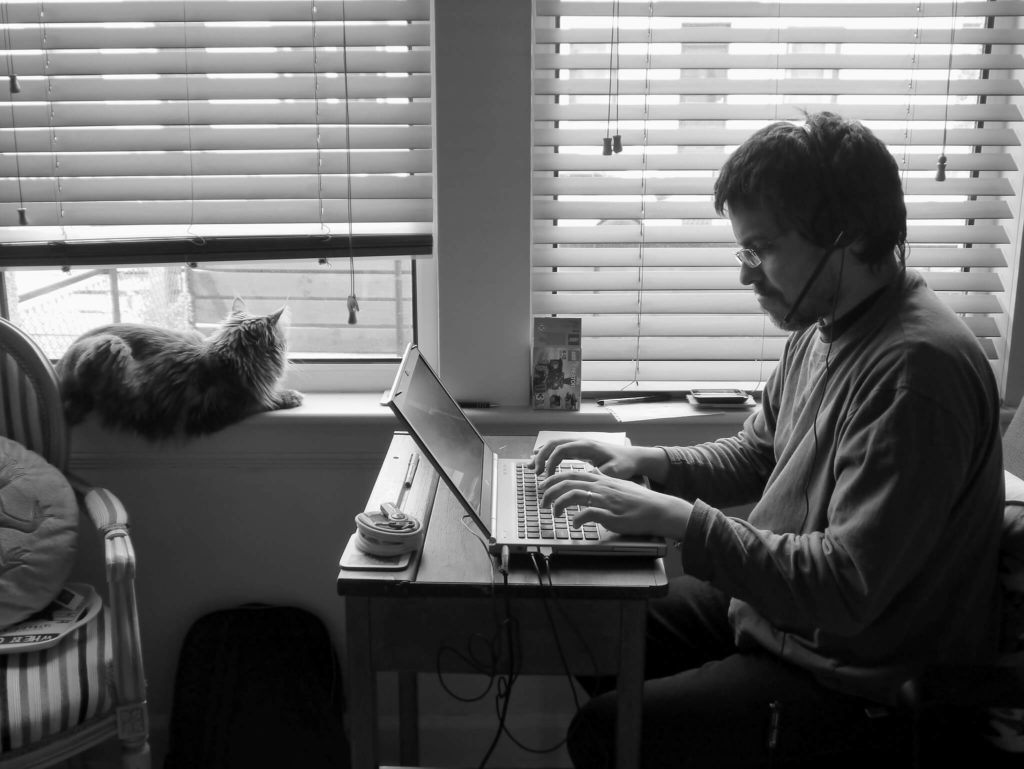 Man working on laptop with cat nearby