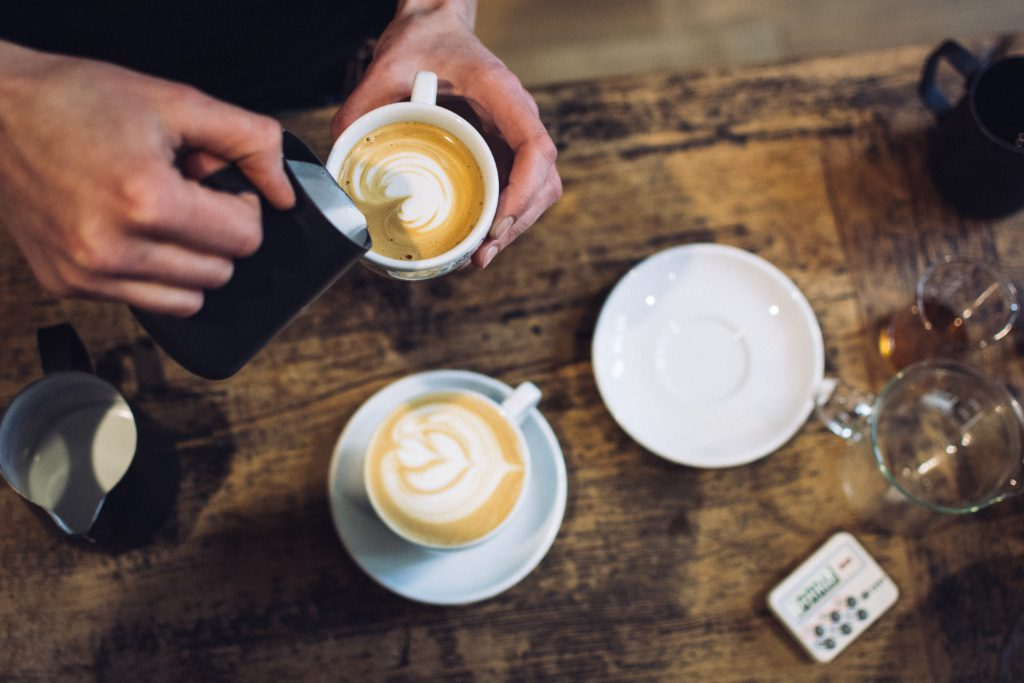 Photo of coffee being poured into cups by Jakub Kapusnak on Unsplash